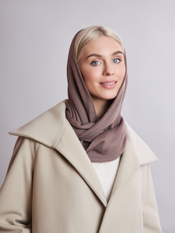 Mujer musulmana europea con cabello rubio en un pañuelo en la cabeza vestida sobre su cabeza. hermosa chica en abrigo con piel suave, cosmética natural