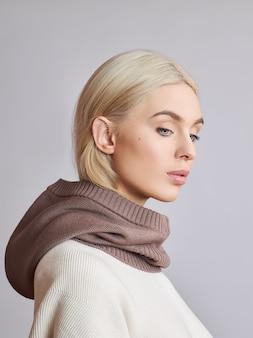 Mujer musulmana europea con el pelo rubio en un capot con capucha vestida sobre su cabeza. hermosa chica en suéter con piel suave, cosmética natural