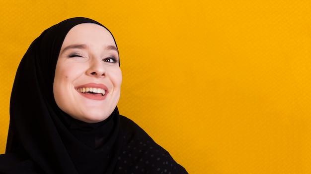 Mujer musulmana feliz parpadeando ojos sobre fondo amarillo