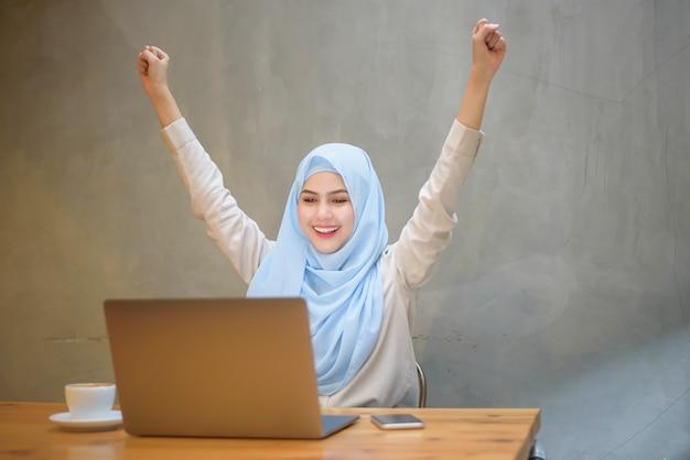 Mujer musulmana con hijab está trabajando con una computadora portátil en la cafetería.