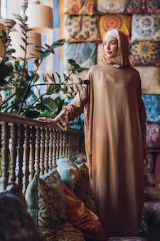 Mujer musulmana joven árabe sentada en un café.