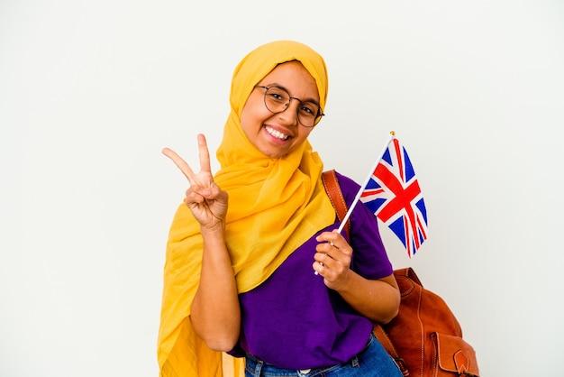 Mujer musulmana joven estudiante aislada en la pared blanca que muestra el número dos con los dedos