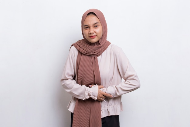 Mujer musulmana joven hermosa asiática enferma que tiene un dolor de estómago aislado en el fondo blanco