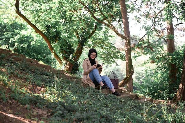 Mujer musulmana leyendo un libro en el parque durante su tiempo libre.