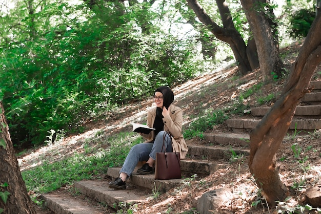 Mujer musulmana leyendo un libro en el parque durante su tiempo libre