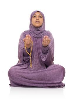 Mujer musulmana mirando hacia arriba orando por alá, niña con traje de oración y rosario, concepto de ramadán kareem