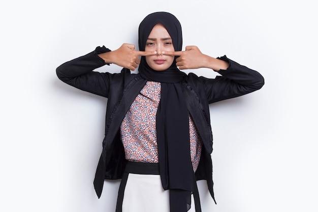 Mujer musulmana de negocios asiáticos tapándose la nariz debido a un mal olor