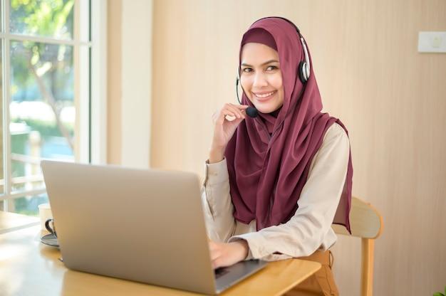 Una mujer musulmana del operador en el auricular que usa la computadora que contesta la llamada del cliente en la oficina, el concepto de servicio al cliente
