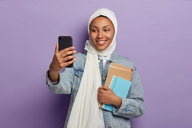 Mujer musulmana positiva con sonrisa agradable, toma selfie en teléfono inteligente moderno, se encuentra con cuaderno espiral y libros de texto aislados en la pared púrpura del estudio