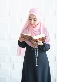 La mujer musulmana que sostiene las cuentas del asimiento de la mano leyó el corán