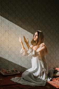 Mujer musulmana rezando con efecto de luz solar