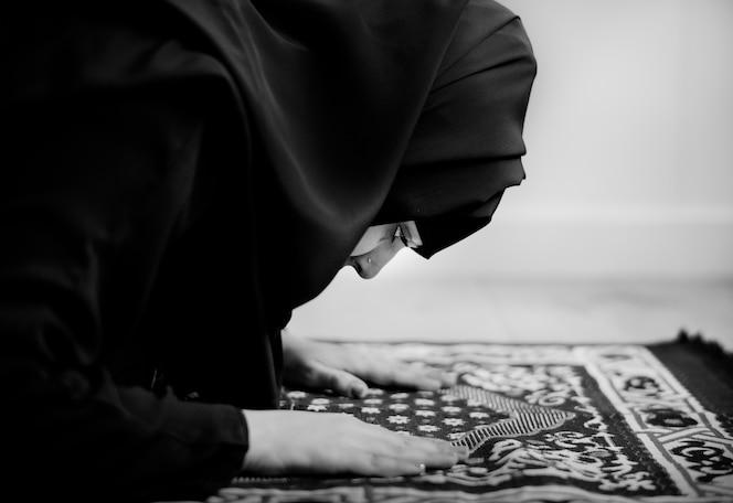 Mujer musulmana rezando en la postura de sujud