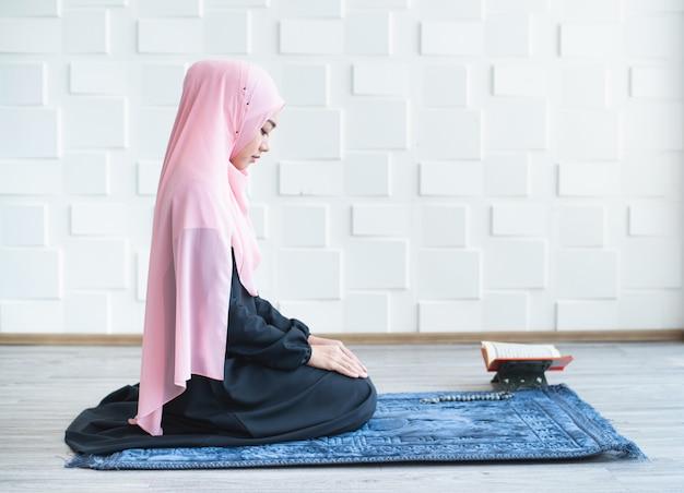 Mujer musulmana rezar en hijab rezando en estera en el interior