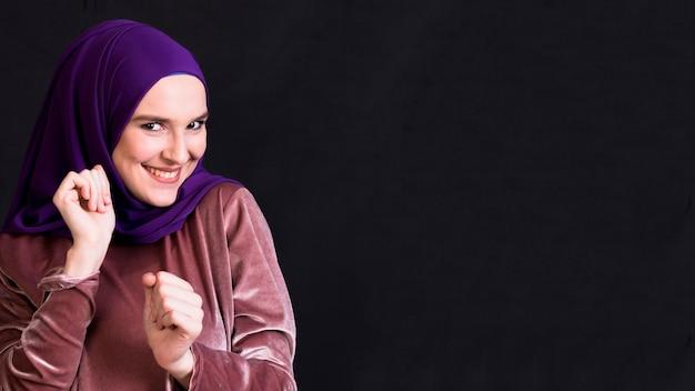 Mujer musulmana sonriente joven que baila en superficie negra