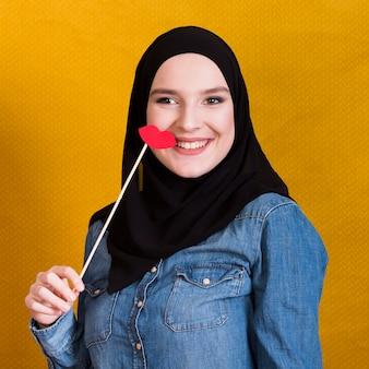Mujer musulmana sonriente sosteniendo un soporte de papel en forma de labios rojos sobre fondo