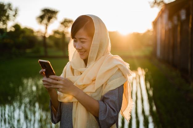 Mujer musulmana con teléfono inteligente al aire libre