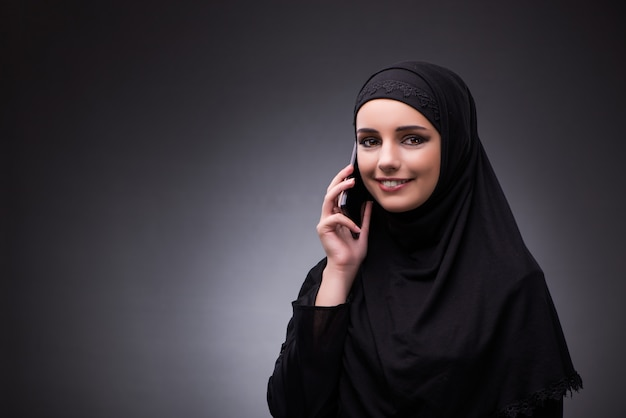 Mujer musulmana en vestido negro sobre fondo oscuro