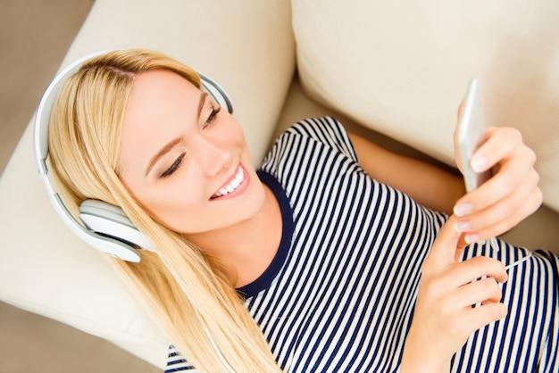 Mujer muy alegre acostado en el sofá y escuchando música en auriculares