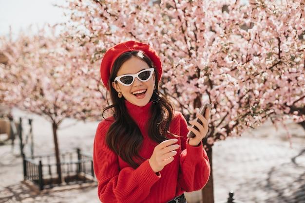 Mujer de muy buen humor posa con el teléfono cerca de los cerezos en flor. retrato de dama de boina roja, suéter de cashemere y anteojos blancos en el jardín en primavera