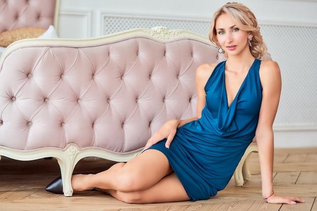 Mujer muy delgada con un elegante vestido azul con un hermoso peinado y zapatos