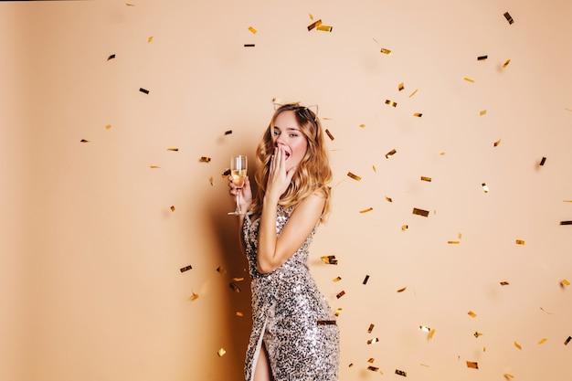 Mujer muy delgada posando bajo confeti brillante en la pared de luz durante la fiesta de año nuevo