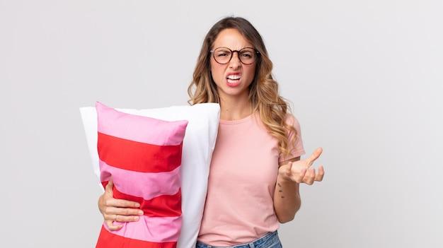 Mujer muy delgada que parece enojada, molesta y frustrada vistiendo pijamas y sosteniendo una almohada