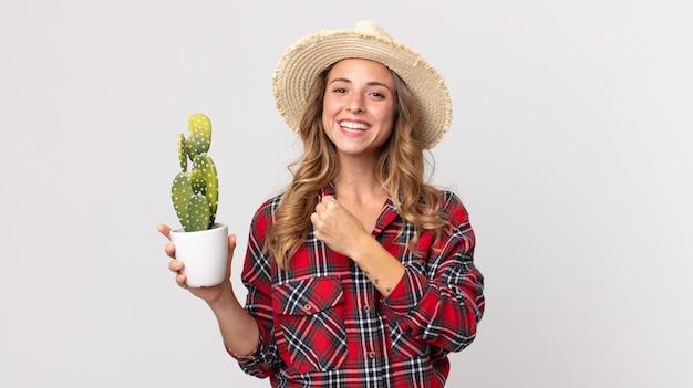 Mujer muy delgada que se siente feliz y enfrenta un desafío o celebra sosteniendo un cactus. concepto de granjero
