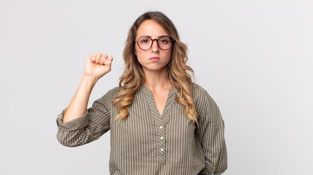 Mujer muy delgada que se siente seria, fuerte y rebelde, levantando el puño, protestando o luchando por la revolución