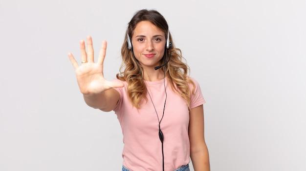 Mujer muy delgada sonriendo y mirando amigable, mostrando el asistente del operador número cinco con un auricular