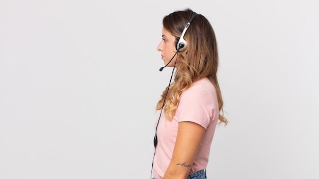 Mujer muy delgada en vista de perfil pensando, imaginando o soñando despierto .asistente del operador con un auricular