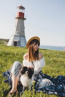 Mujer muy elegante en el campo, sosteniendo un perro, feliz estado de ánimo positivo, verano, sombrero de paja, traje de estilo bohemio