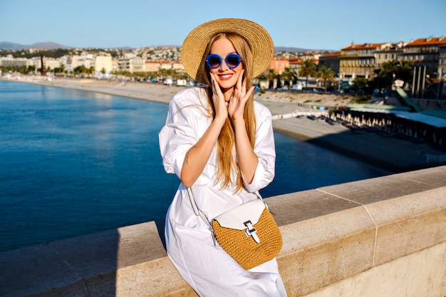 Mujer muy elegante con vestido blanco, sombrero de paja y bolso posando cerca del océano