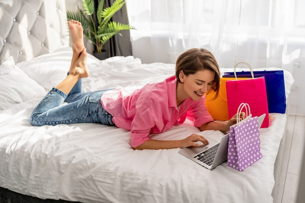 Mujer muy feliz acostado en la cama en casa con coloridas bolsas de compras comprando en línea usando laptop