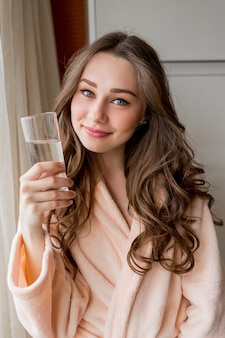 Mujer muy feliz en bata de baño bebiendo agua dulce en casa