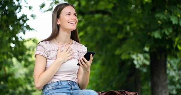 Mujer muy feliz leyendo buenas noticias a través de su teléfono inteligente