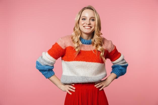 Una mujer muy hermosa joven emocionada feliz que presenta aislada sobre la pared rosada