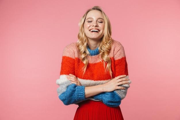 Una mujer muy hermosa joven emocionada feliz que ríe posando aislada sobre la pared rosada