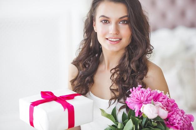 Mujer muy hermosa con peonía y caja de regalo en el interior