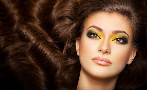 Mujer muy sexy con cabello hermoso, maquillaje expresivo y piel limpia
