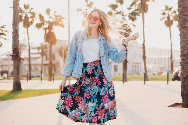 Mujer muy sonriente caminando en las calles de la ciudad con elegante falda estampada y chaqueta vaquera de gran tamaño con gafas de sol rosas, tendencia de estilo veraniego