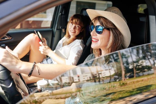 Mujer muy sonriente conduciendo coche