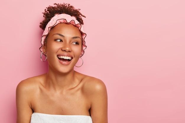 Mujer muy sonriente mira en soportes del lado derecho envueltos en una toalla con los hombros desnudos lleva gorro de ducha disfruta de tomar un baño y relajarse