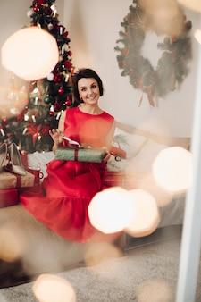 Mujer muy sonriente sentada en su dormitorio con regalo de navidad