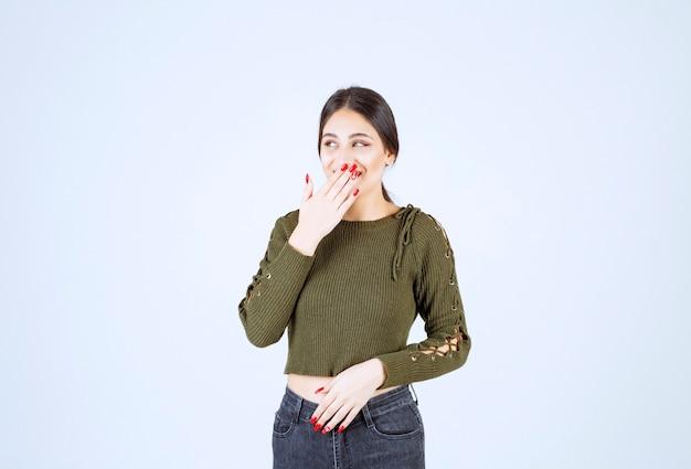 Mujer muy sonriente tapándose la boca en la pared blanca