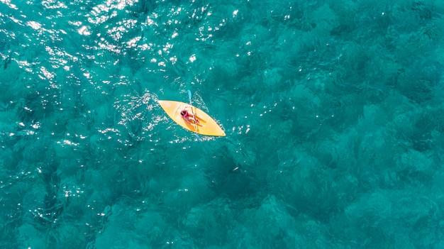 La mujer nada en un kayak deportivo en un océano exótico turquesa claro.