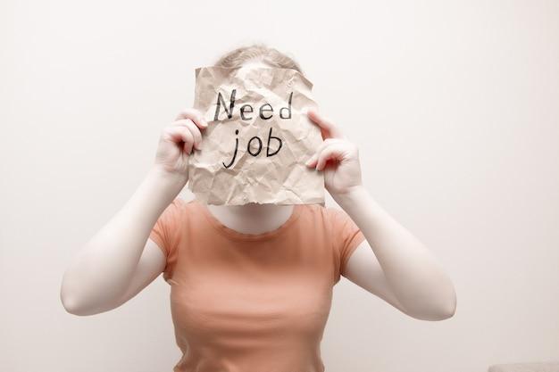 Mujer en naranja tonto sostiene un trozo de papel de regalo marrón arrugado con la inscripción necesita trabajo