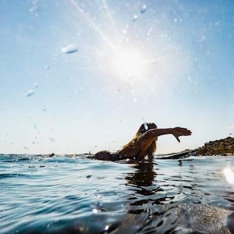 Mujer, natación, en, tabla de surf, en, agua