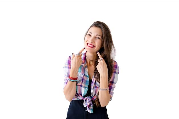 Mujer natural alegre apuntando con los dedos en las mejillas