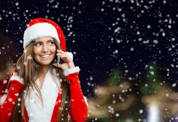 Mujer de navidad haciendo una llamada usando su teléfono móvil