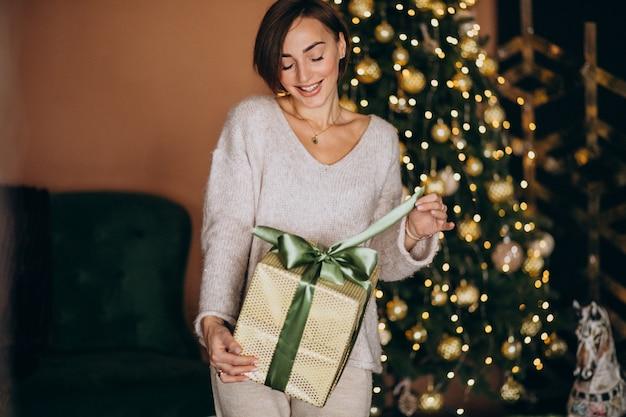 Mujer en navidad sosteniendo un regalo de navidad junto al árbol de navidad